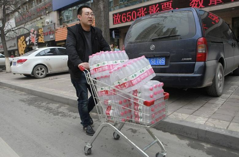 A man pushes a shopping cart filled with bottled waters after reports on heavy levels of benzene in local tap water, in Lanzhou, Gansu province April 11, 2014. REUTERS/Stringer