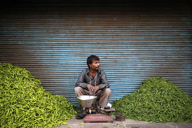 A vendor waits for customers next to heaps of green chillies at a vegetable wholesale market along a roadside in the old quarters of Delhi April 15, 2014.  REUTERS/Anindito Mukherjee