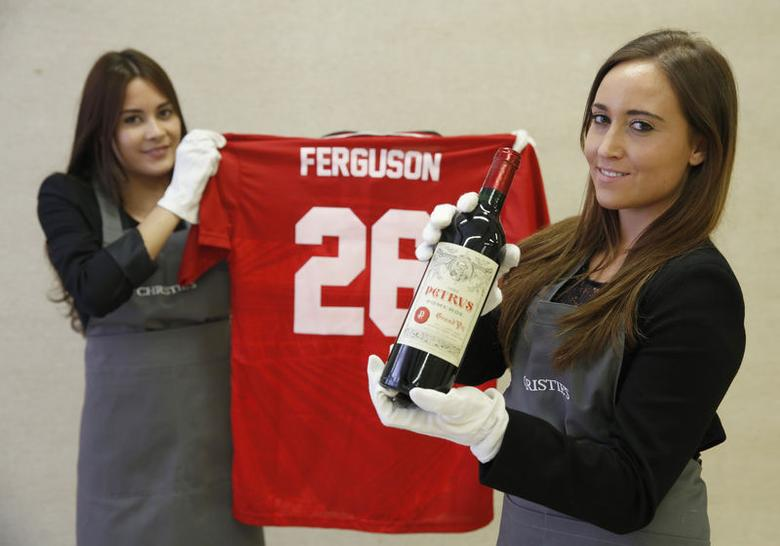 Employees pose with a bottle of ''Petrus 1988'' wine and a Manchester United Retro Champions League shirt from 1999 signed by retired boss Alex Ferguson, at Christie's auction house in London April 14, 2014. REUTERS/Luke MacGregor