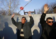 Пророссийские активисты стоят с поднятыми руками у авиабазы в Краматорске 15 апреля 2014 года. Госдепартамент США сообщил во вторник, что ожидает новых связанных с событиями на Украине санкций против России, но хочет подождать международного саммита в Женеве на этой неделе в надежде на дипломатическое урегулирование. REUTERS/Marko Djurica