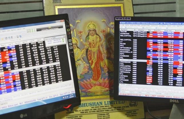 An image of Lakshmi, the Hindu goddess of wealth and prosperity, is placed between monitors displaying share price index at a share trading market in Chandigarh August 29, 2013. REUTERS/Ajay Verma/Files