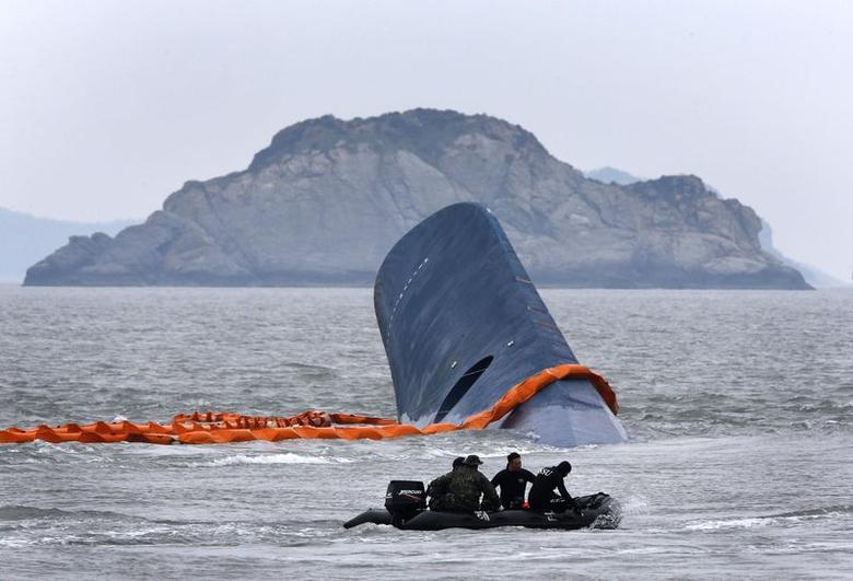 A vessel involved in salvage operations passes near the upturned South Korean ferry ''Sewol'' in the sea off Jindo April 17, 2014. REUTERS/Kim Kyung-Hoon