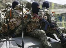 Armed men, wearing black and orange ribbons of St. George - a symbol widely associated with pro-Russian protests in Ukraine, drive an armoured personnel carrier in Slaviansk April 18, 2014. The self-declared leader of pro-Russian separatists in eastern Ukraine, Denis Pushilin, on Friday said that he did not consider his men to be bound by an agreement between Russia and Ukraine to disarm and vacate occupied buildings.  REUTERS/Gleb Garanich  (UKRAINE - Tags: POLITICS CIVIL UNREST MILITARY)