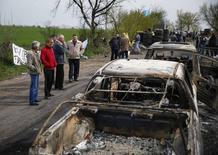Местные жители смотрят на сгоревшие машины на блокпосту около украинского города Славянск, который стал местом столкновений в ночь на воскресенье, 20 апреля 2014 года. REUTERS/Gleb Garanich