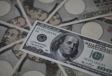 Купюры валюты иена и доллар в Токио 28 февраля 2013 года. Курс доллара к иене поднимается, но рост сдерживается напряженной ситуацией на Украине. REUTERS/Shohei Miyano