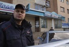 Сотрудники полиции у отделения банка Западный в Белгороде 21 апреля 2014 года. Мужчина с охотничьим ружьем, захвативший в понедельник утром офис лишенного лицензии российского банка, сдался властям, не тронув находившихся в отделении сотрудников, сообщила полиция. REUTERS/Vladimir Kornev
