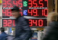 Люди проходят мимо пункта обмена валюты в Москве 3 апреля 2014 года. Рубль торговался с минимальными изменениями на сессии понедельника после утреннего ослабления в ответ на рост напряженности на востоке Украины в минувшие выходные, при этом активность и ликвидность валютного рынка были пониженными из-за пасхальных каникул на европейских площадках. REUTERS/Maxim Shemetov