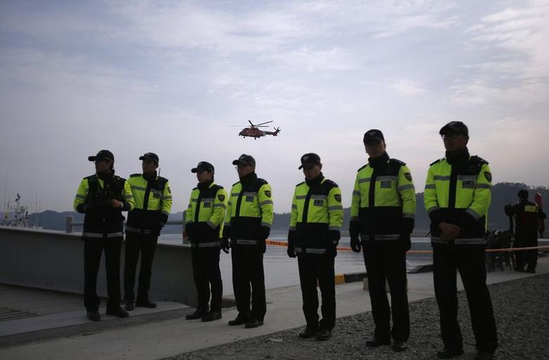 Police officers are seen as a rescue and salvage team helicopter (top) flies over a port where family members of missing passengers from the capsized passenger ship Sewol gathered to wait for news from rescue and salvage teams, in Jindo April 22, 2014. REUTERS/Kim Hong-Ji