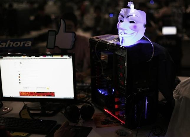 A Guy Fawkes mask is seen on a computer as a man surfs the web during a ''Campus Party'' Internet users gathering in Sao Paulo January 30, 2013. REUTERS/Nacho Doce/Files