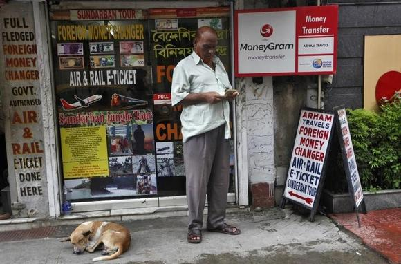 A customer counts currency outside a currency exchange shop in Kolkata August 29, 2013.  REUTERS/Rupak De Chowdhuri/Files