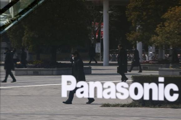 People are reflected in a sign at Panasonic Center Tokyo in Tokyo March 12, 2014. REUTERS/Toru Hanai/Files