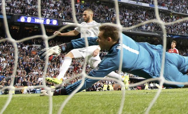 Real Madrid's Karim Benzema (L) scores against Bayern Munich's goalkeeper Manuel Neuer during their Champions League semi-final first leg soccer match at Santiago Bernabeu stadium in Madrid April 23, 2014.  REUTERS/Darren Staple