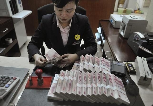 A clerk counts 100 Chinese yuan banknotes at a branch of China Merchants Bank in Hefei, Anhui province March 17, 2014. REUTERS/Stringer/Files