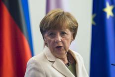 Канцлер Германии Ангела Меркель общается с прессой в Берлине 25 апреля 2014 года.  Высокая статуя советского солдата в берлинском Трептов-парке, держащего на руках немецкую девочку и наступающего на нацистскую свастику, напоминает жителям Германии о долге перед Россией. REUTERS/Thomas Peter