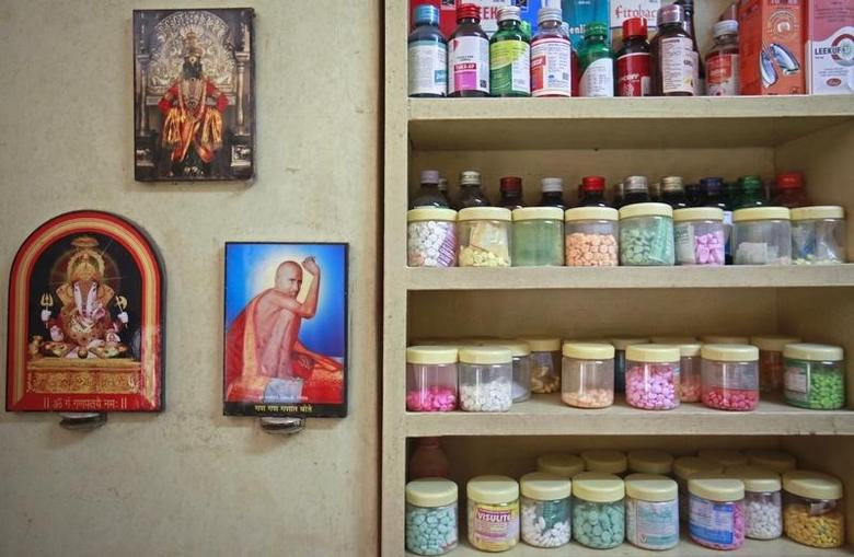 Pictures of Hindu gods hang beside a medicines rack inside a clinic in Pune August 27, 2012. REUTERS/Danish Siddiqui/Files