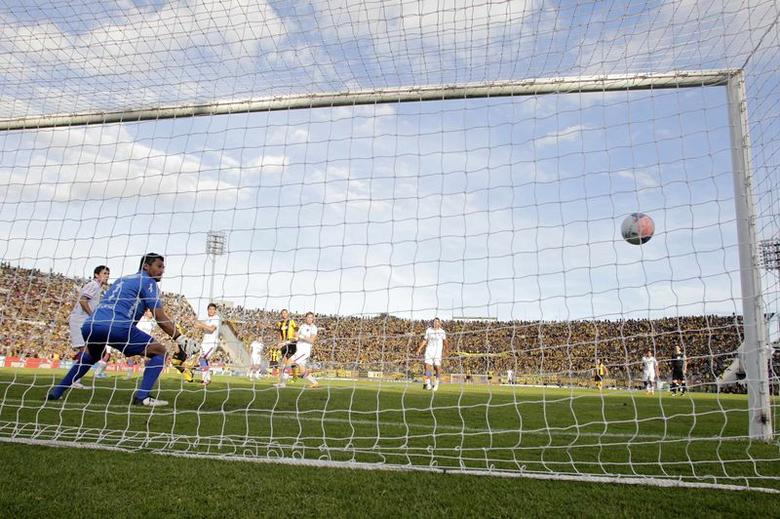 Nacional's goalkeeper Gustavo Munua (2nd L) looks on as Penarol's Fabian Macaluso (4th L) scores a goal during their Uruguayan tournament soccer match in Montevideo, April 27, 2014. REUTERS/Andres Stapff