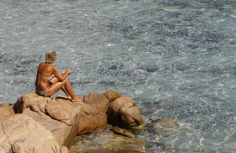 A woman sits by the rocks at the Ramizzo beach in the so called ''Emerald Coast'' of the Sardinia island in Italy July 7, 2011. REUTERS/Max Rossi
