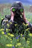 Миротворец следит с помощью бинокля за входом сил безопасности Югославии в сербскую деревню Муховац 24 мая 2001 года. НАТО не видит признаков того, что десятки тысяч российских солдат отходят от приграничных с Украиной районов, сообщил во вторник представитель блока, несмотря на утверждение Москвы о том, что она возвращает войска на исходные позиции. REUTERS/Hazir Reka