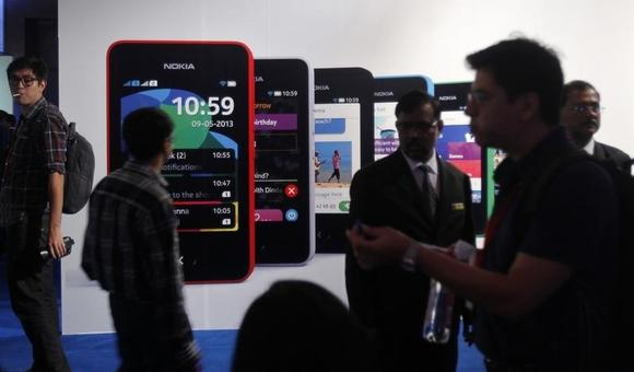 Visitors gather during the unveiling of Nokia's new $99 phone in its mid-range Asha line at a launch in New Delhi May 9, 2013. REUTERS/Anindito Mukherjee/Files