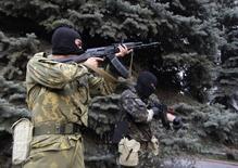 Пророссийские активисты с автоматами у управления милиции в Луганске 29 апреля 2014 года. Пророссийские сепаратисты открыли огонь из автоматов по областному управлению милиции в Луганске на востоке Украины, где правоохранители отказались перейти на сторону повстанцев и сдать оружие, сообщил фотокорреспондент Рейтер с места событий.  REUTERS/Vasily Fedosenko