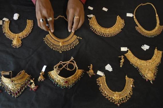 A shop attendant displays gold necklaces for the camera at a jewellery shop in Hyderabad June 30, 2009. REUTERS/Krishnendu Halder/Files