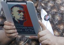 Участник акции протеста держит в руках планшет с изображением Алексея Нвального в Москве 10 мая 2012 года. Верхняя палата послушного Кремлю российского парламента во вторник поддержала поправки, которые ужесточают правила для блогеров и рассматриваются критиками как попытка президента Владимира Путина удушить инакомыслие в интернете. REUTERS/Denis Sinyakov