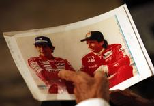 Former Brazilian Formula One driver Emerson Fittipaldi holds a picture of Ayrton Senna during an interview with Reuters in Sao Paulo April 10, 2014.  REUTERS/Paulo Whitaker