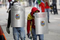 Anti-government protesters cover themselves with shields during riots in Caracas April 17, 2014.  REUTERS/Christian
