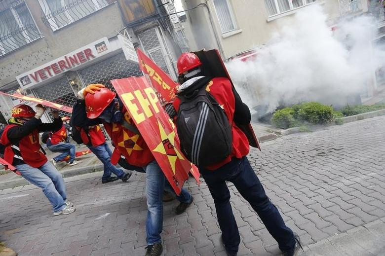 Protesters shield themselves from tear gas fired by riot police during a May Day demonstration in Istanbul May 1, 2014.  REUTERS/Murad Sezer