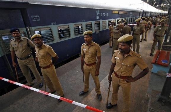 Policemen stand guard next to a passenger train in which two explosions occurred, at the railway station in Chennai May 1, 2014. REUTERS/Babu