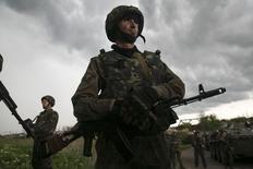 Украинский солдат стоит напротив местных жителей на блокпосту около украинского Славянска, 2 мая 2014 года. Операция украинских правоохранителей против сепаратистов в мятежном Славянске на востоке страны и столкновения пророссийских и проукраинских активистов в черноморской Одессе привели к новым жертвам в пятницу. REUTERS/Baz Ratner (UKRAINE - Tags: POLITICS CIVIL UNREST) - RTR3NJI5