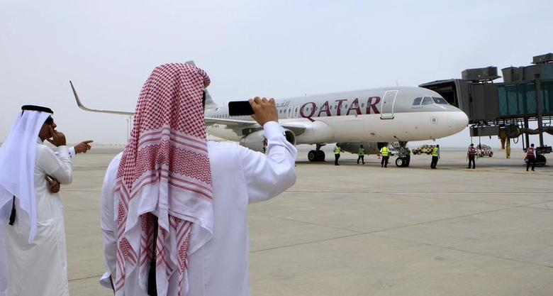 Qatari men take pictures after the Airbus A320-200 aircraft chartered by Qatar Airways landed at Doha's new Hamad International Airport (HIA), April 30, 2014. REUTERS/Fadi Al-Assaad