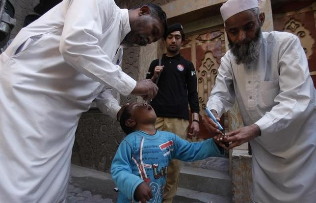 Polio workers give polio vaccine drops to a child as a policeman stands guard during a vaccination campaign in Peshawar, the capital of Khyber-Pakhtunkhwa province March 30, 2014.  REUTERS/Fayaz Aziz