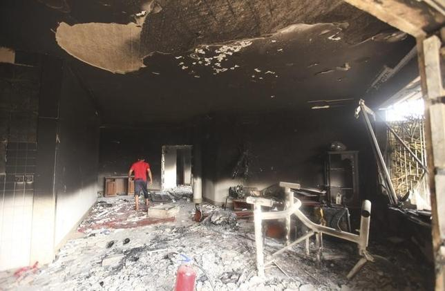 A man walks inside the U.S. consulate, which was attacked and set on fire by gunmen , in Benghazi September 12, 2012. REUTERS/Esam Al-Fetori/Files