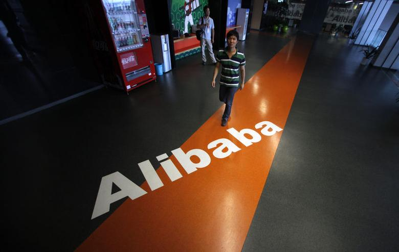 An employee walks pass a logo of Alibaba during a media tour organised by government officials at its headquarters on the outskirts of Hangzhou, Zhejiang province, June 20, 2012. REUTERS/Carlos Barria/Files