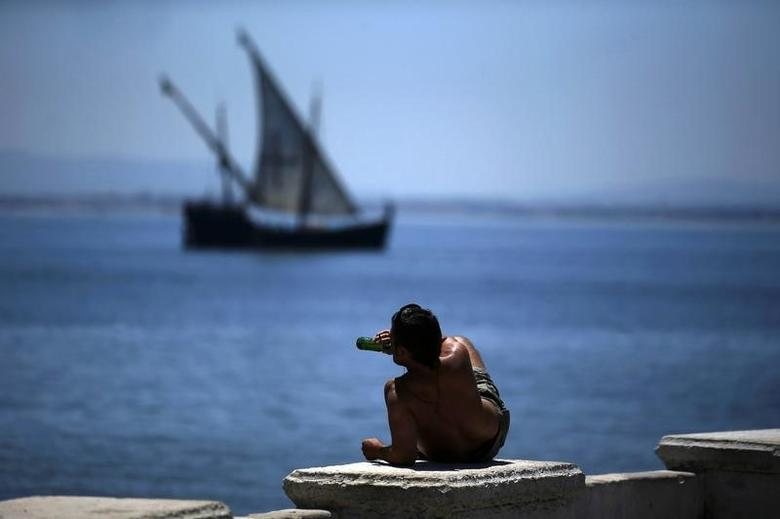 A man drinks beer at the ''Cais das Colunas'', as a caravel sails at the Tagus River in Lisbon July 4, 2013.  REUTERS/Rafael Marchante (PORTUGAL - Tags: SOCIETY TRAVEL) - RTX11CEV