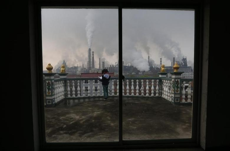 A girl reads a book on her balcony as smoke rises from chimneys of a steel plant, on a hazy day in Quzhou, Zhejiang province April 3, 2014.  REUTERS/Stringer