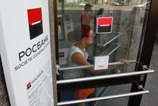 Женщина выходит из офиса Росбанка в Москве 15 мая 2013 года. Чистая прибыль Societe Generale снизилась на 13,3 процента в первом квартале 2014 года до 315 миллионов евро ($439 миллионов), несмотря на 14-процентное повышение выручки. REUTERS/Maxim Shemetov