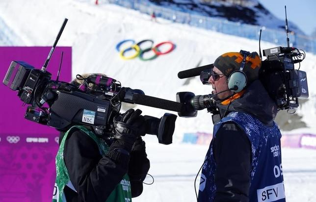 Media cameramen shouldering video cameras chat during the women's snowboard slopestyle qualifying round at the 2014 Sochi Olympic Games in Rosa Khutor February 6, 2014. REUTERS/Mike Blake