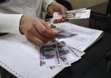 Кассир считает рубли в почтовом отделении в Симферополе 25 марта 2014 года. Рубль подешевел утром четверга после существенного укрепления накануне в условиях невысокой активности на рынке в преддверии майских праздников и ожиданий возможной реакции Запада на заявления Путина на вчерашней встрече с ОБСЕ. REUTERS/Shamil Zhumatov