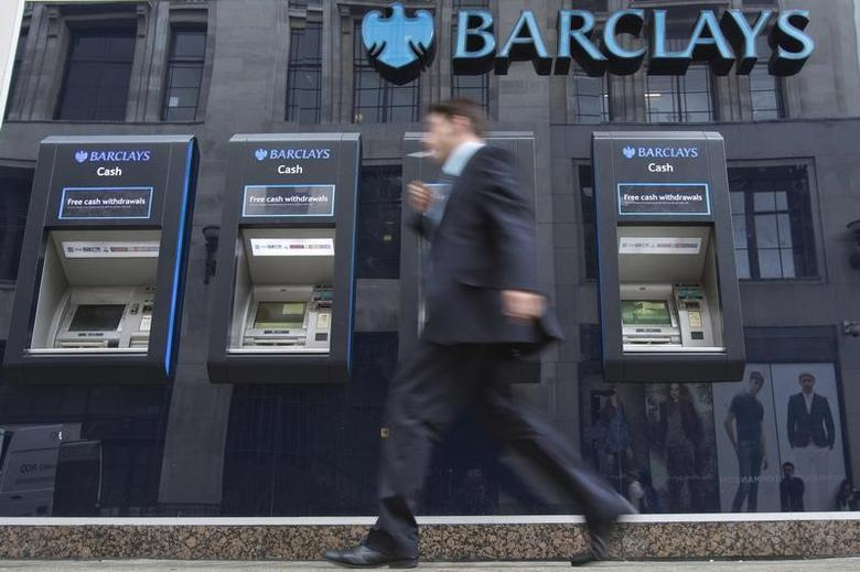 A man passes automated teller machines at a Barclays bank branch in London August 30, 2012. REUTERS/Neil Hall/Files
