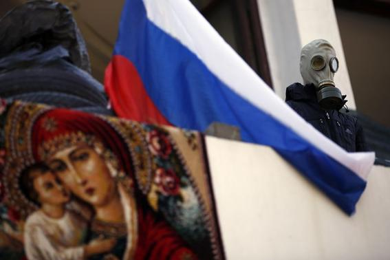 A pro-Russia rebel wearing a gas mask stands beside a Russian flag on the balcony of the city hall in Mariupol, eastern Ukraine May 7, 2014. REUTERS/Marko Djurica