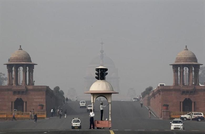 A traffic police officer directs traffic in front of India's presidential palace Rashtrapati Bhavan amid dense smog in New Delhi November 14, 2012.  REUTERS/B Mathur