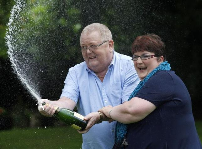 Colin Weir (L) and his wife Chris spray a bottle of champagne after a news conference at a hotel near Falkirk, Scotland July 15, 2011. REUTERS/David Moir