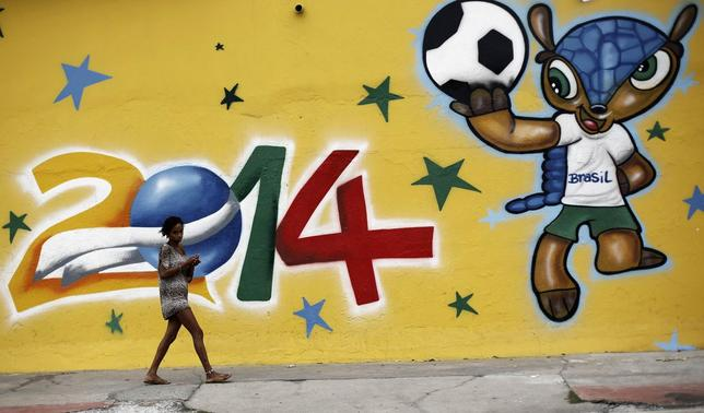 A woman walks past a graffiti painted with the official mascot of the 2014 World Cup, Fuleco the Armadillo, in Sao Paulo May 7, 2014.   REUTERS/Nacho Doce