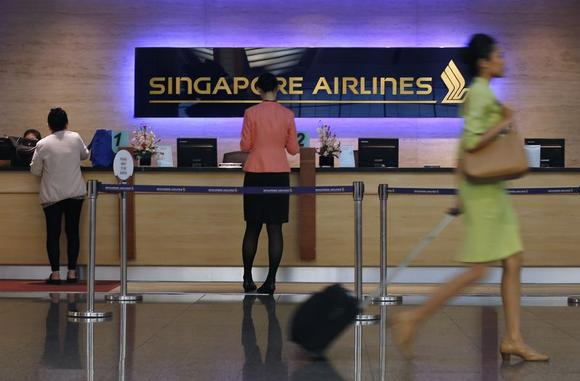 People walk past a Singapore Airlines ticketing counter at Changi Airport in Singapore May 7, 2014.  REUTERS/Edgar Su
