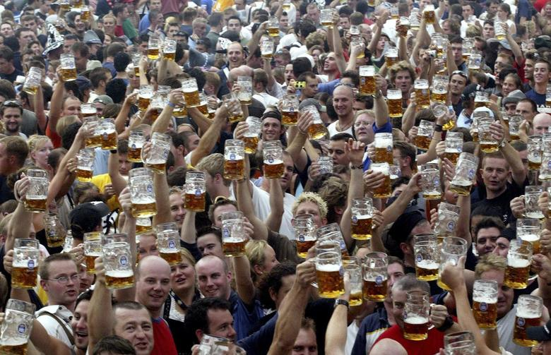 Visitors toast with their one-liter beer mugs during the opening day of the Munich Oktoberfest beer festival in this September 20, 2003 file photo. REUTERS/Michael Dalder/Files