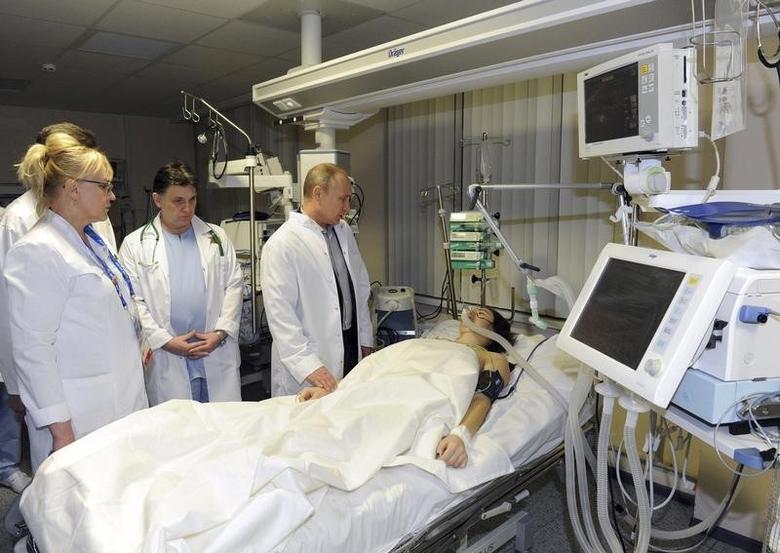 Russia's President Vladimir Putin (R) visits Russian Olympic skicross racer Maria Komissarova at a hospital in Sochi, February 15, 2014. REUTERS/Mikhail Klimentyev/RIA Novosti/Kremlin
