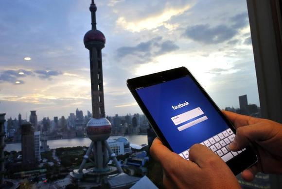 In this photo illustration, a man holds an iPad with a Facebook application in an office building at the Pudong financial district in Shanghai, September 25, 2013. REUTERS/Carlos Barria/Files