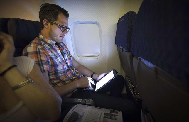 A passenger uses a wireless tablet on an American Airlines airplane, which is equipped with Gogo Inflight Internet service, enroute from Miami to New York December 10, 2013. REUTERS/Carlo Allegri/Files